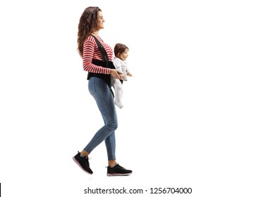 Full lenght shot of a young mother with a baby in a carrier walking isolated on white background