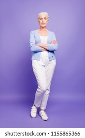 Full lenght size body vertical portrait of grey haired old confident woman wearing casual, shoes footwear, with folded arms. Isolated over violet purple background