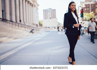 Full lengt portrait of successful african american businesswoman dressed in formal wear posing and smiling at camera in downtown.Prosperous student of faculty of law standing near university building