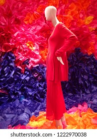 full length 3/4 side view of white plain mannequin in lon red dress, with colorful graphic background