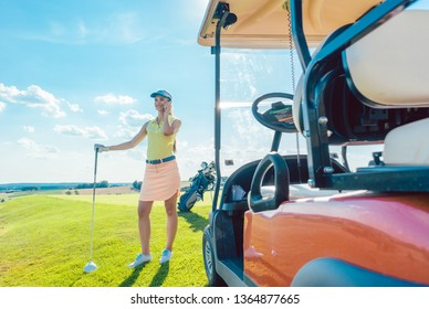 Full length of an active and cheerful woman, wearing modern golf apparel while talking on mobile phone on the golf course near the cart in a sunny day of summer