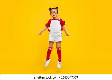 Full length adorable little girl in bright trendy outfit and sunglasses smiling and leaping up against yellow background