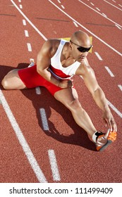 Full length of African American male athlete stretching on racetrack
