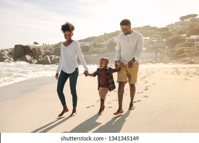 Full length of african family of three walking along the sea shore. Parents holding hands of son and walking on beach.