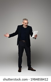 full length of angry middle aged businessman with grey hair screaming while looking at digital tablet on grey