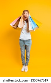 Full length annoyed girl feeling tired from shopping, woman with lots of bags, beautiful girl with bags on yellow background
