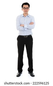 Full length Asian businessman arms crossed standing isolated on white background.