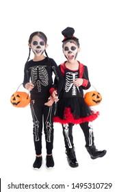 Full length of asian girls in skeleton costume holding halloween pumpkin bucket,standing and smile over white background