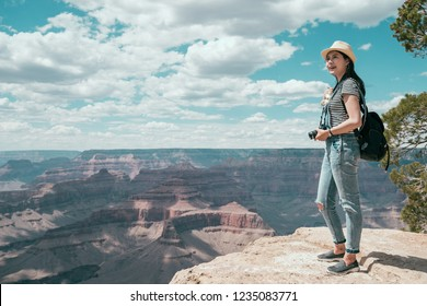 full length of asian traveler on hiking travel. young photographer enjoy the beautiful view on grand canyon national park. Joyful woman travel vacation in america.