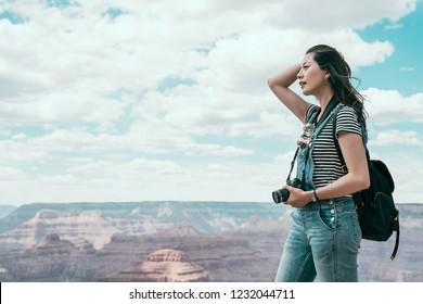 full length of asian traveler standing on the top of grand canyon national park on hiking travel. lady lens man standing and sightseeing the desert mountain. hiker flicks hair on sunny day blue sky.