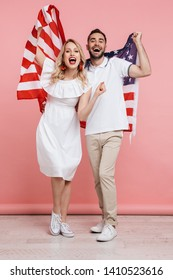 Full length of an attractive cheerful young couple standing together isolated over pink background, carrying american flag