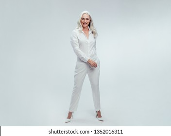 Full length of attractive mature woman standing over white background. Beautiful senior woman posing in white casuals.
