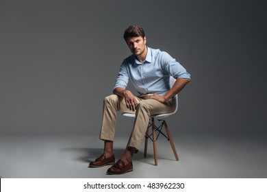 Full length of attractive serious young man in blue shirt sitting on chair over grey background