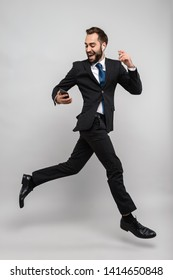 Full length of an attractive smiling young businessman wearing suit jumping isolated over gray background, wearing earphones, holding mobile phone