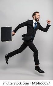 Full length of an attractive smiling young businessman wearing suit isolated over gray background, carrying briefcase, running