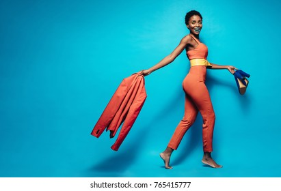 Full length of attractive woman in stylish clothing. African female fashion model walking over blue background jacket and shoes in hand.