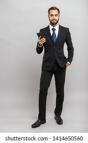 Full length of an attractive young businessman wearing suit standing isolated over gray background, holding mobile phone