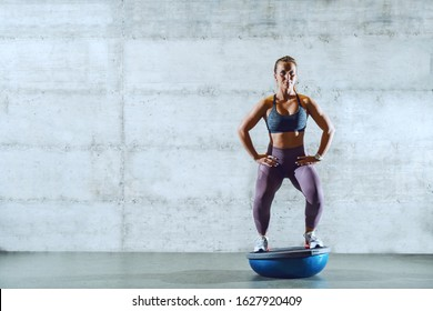 Full length of attractive young caucasian sportswoman in sportswear with ponytail standing on bosu ball and doing squat endurance,