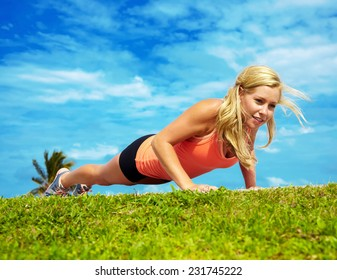 Full length of attractive young woman doing pushup exercise at park