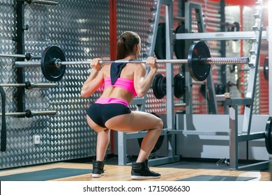 Full length back view of muscular girl with sexy buttocks performing squat exercises with a barbell in modern gym wearing pink and black sportswear
