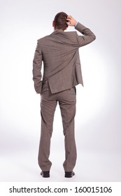 full length back view picture of a young business man scratching his head while holding a hand in his pocket. on a gray background
