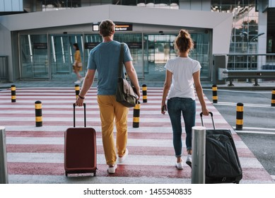 Full length back view portrait of gentleman and lady carrying their trolley bags and using pedestrian crossing. They heading to the entrance of airport terminal