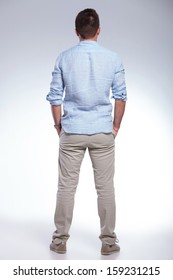 full length back view portrait of a young casual man with both hands in pockets. on gray background