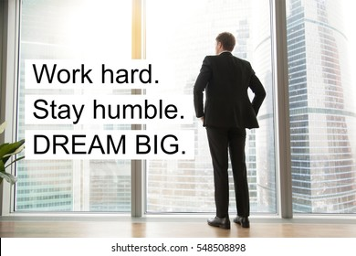 "Full length back view of successful businessman in suit standing in office with hands on his waist. Photo with motivational text ""Work hard. Stay humble. Dream big"""