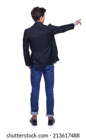 Full length back view of young trendy man pointing to the side on blank copy space, over white background