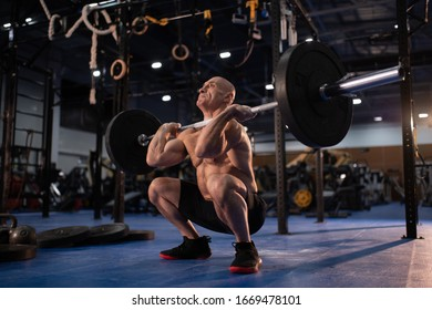 Full length bald elderly man in great shape doing front squat with heavy barbell while performing clean and jerk movement during weightlifting workout in contemporary gym