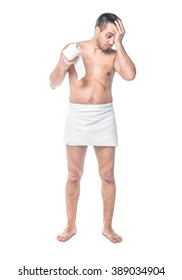 Full length bare body of disappointed man standing and holding toilet paper, isolated on white background, studio shot.