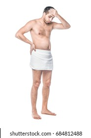 Full length bare body of disappointed man standing with towle oround his waist, isolated on white background, studio shot.