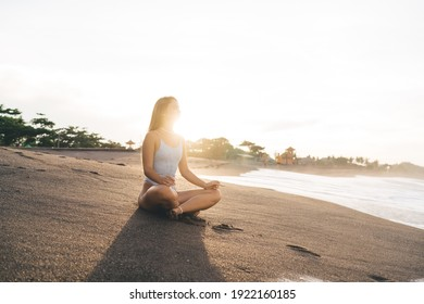 Full length of barefoot female in swimwear relaxing on sandy beach near calm sea water while meditating during bright sunset