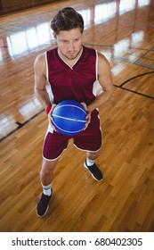 Full length of basketball player with ball practicing in court