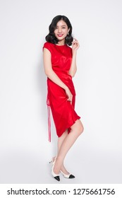 Full length of beautiful asian woman in dress standing and posing over white background