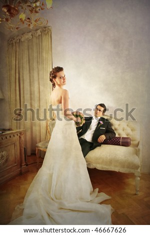 Full length of beautiful bride and groom in luxurious with vintage look interior and dress seen from the rear side