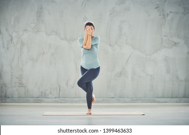 Full length of beautiful Caucasian brunette standing on the mat barefoot in Eagle yoga pose.