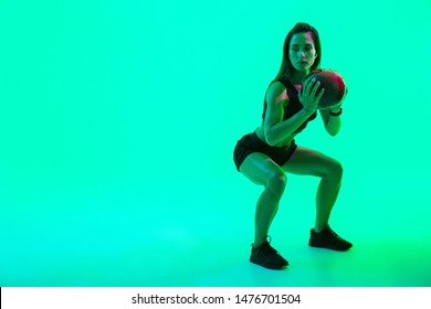 Full length of a beautiful confident young fitness girl standing isolated over green neon background, wearing wireless earphones, working out with a medicine ball, squatting