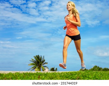Full length of beautiful female athlete jogging on sidewalk at beach