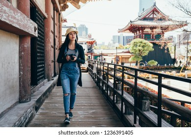 full length of a beautiful girl photographer walking in historic japanese temple building outdoor. young lady tourist holding camera visiting shitennoji osaka japan. asian student travel in summer.