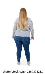 Full length of beautiful plus size young overweight woman wearing jeans and shirt isolated on white background. Posing backwards looking at wall.