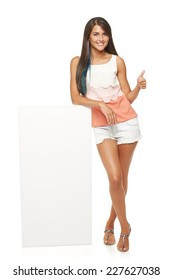 Full length of beautiful tanned woman in shorts standing leaning on white blank advertising board banner and showing approving sign, over white background