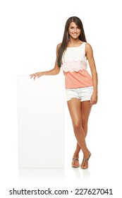 Full length of beautiful tanned woman in shorts standing leaning on white blank advertising board banner, over white background