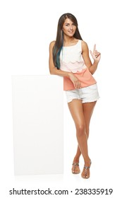 Full length of beautiful tanned woman in shorts standing leaning on white blank advertising board banner and showing finger up, over white background