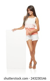 Full length of beautiful tanned woman in shorts standing leaning on white blank advertising board banner and pointing at it, over white background