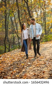 Full length of a beautiful young couple in love walking at the autumn park, holding hands