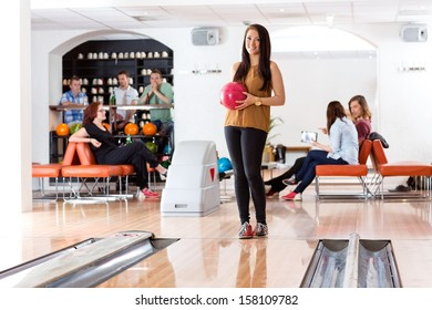 Full length of beautiful young woman holding bowling ball with people in background