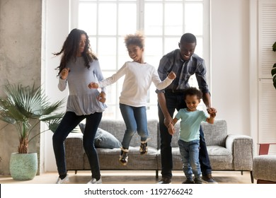 Full length black African whole family have a fun. Married couple with little kids toddler son preschool daughter dancing moving in living room at new home. Happy family spend time together concept