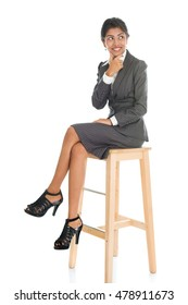 Full length black businesswoman sitting on high chair and having a thought, isolated on white background.