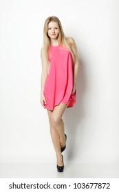 Full length of blond female in pink dress posing